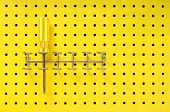 One yellow Phillips screwdriver sits in a rack on a yellow pegboard. poster