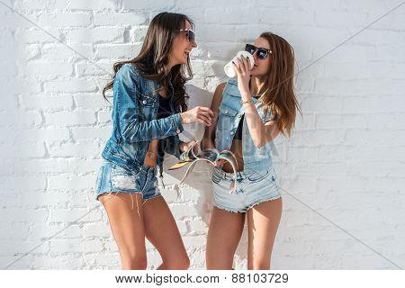 two pretty girls wearing sunglasses in summer jeanswear street urban casual style talking, laughing