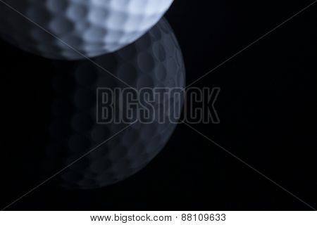 Close up of golf ball with reflection isolated on black background, copy space for text.