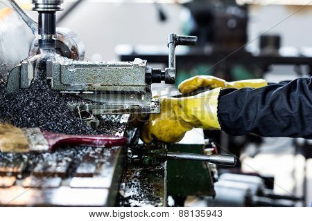 worker working withdrilling machine in factory workshop