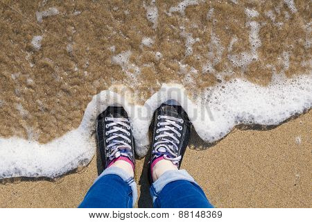 Standing at the edge of the sea on a beach