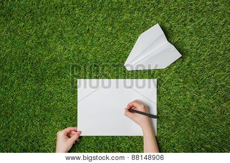 Writing on blank sheet of paper with airplane nearby