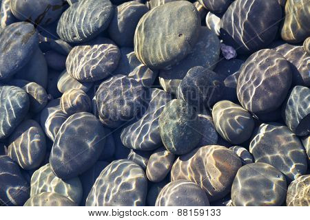 Multicolored pebbles and cobblestones in a stream with sunlight diffraction patterns from surface ripples useful as a background or a texture. poster
