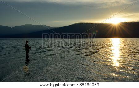 Fisherman Fishing In Mcdonald Lake In Glacier National Park At Sunset