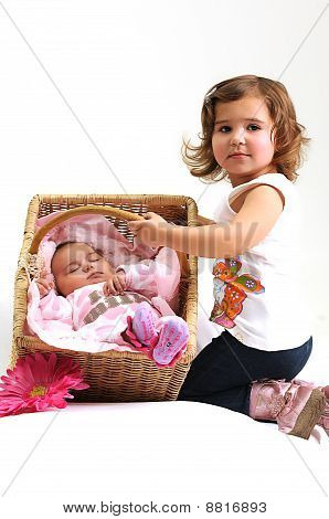 two sisters playing and smiling in a basket
