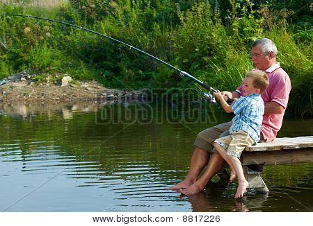 Photo of grandfather and grandson sitting on pontoon with their feet in water and fishing on weekend poster
