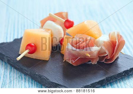 Appetizer canape with melon, cheese ball and prosciutto poster