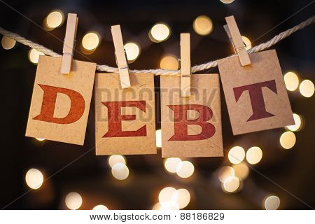 The word DEBT printed on clothespin clipped cards in front of defocused glowing lights. poster