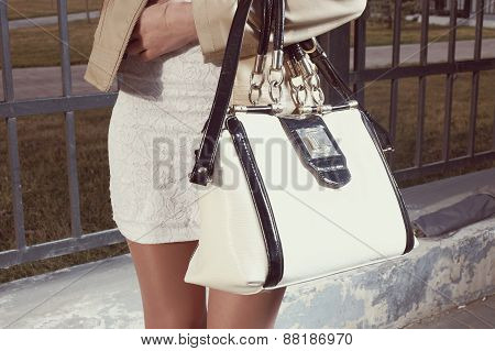 Fashion young woman with handbag and white skirt near street fence closeup, part of the body, instagram color poster