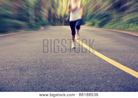 fitness woman legs running at forest road