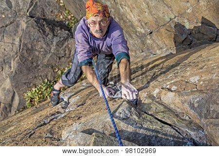 Aged rock climber Mature male extreme climber climbs the rocky wall poster
