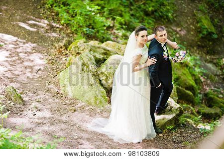 Gorgeus Wedding Couple On Green Sunny Forest On Stones