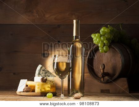 White wine with various types of cheese on wooden background