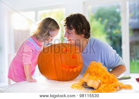 Father And Child Carving Pumpkin For Halloween