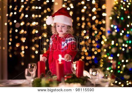 Little Girl Lighting Candles At Christmas Dinner