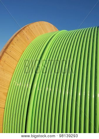 Green fiber optic NBN cable on a timber drum