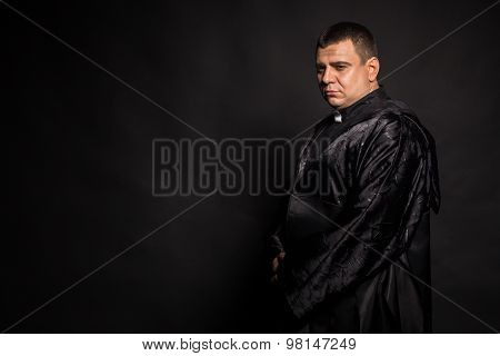 The priest. An actor dressed as a Catholic priest