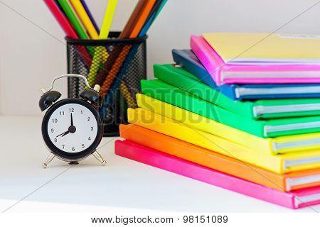 Black alarm clock. Multi colored books in stack