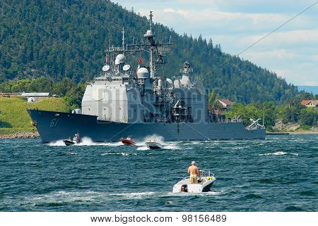 People in motorboats follow norwegian military ship in a fjord in Frogn, Norway.
