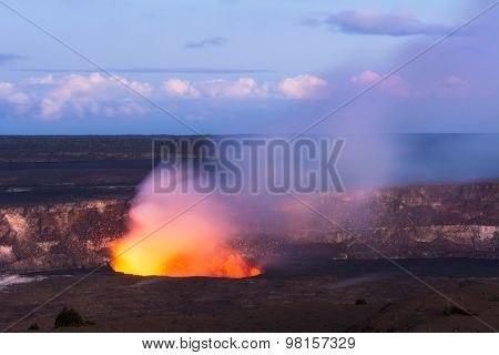 As the sun sets Kilauea volcano begins to show the hot lava glow of its active vent, spewing out smoke as the molten rock burns.