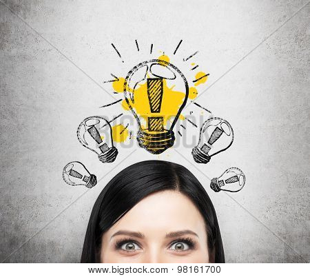 A Head Of Young Brunette Lady Who Is Thinking About New Business Ideas. A Light Bulb Are Drawn On Th