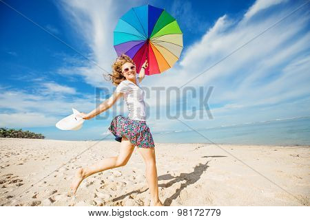 Cheerful young girl with rainbow umbrella having fun on the beach
