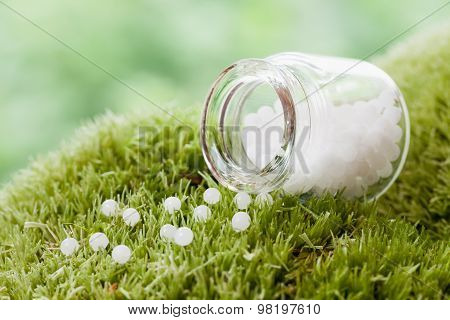 Bottle Of Homeopathy Globules On Green Moss. Selective Focus.
