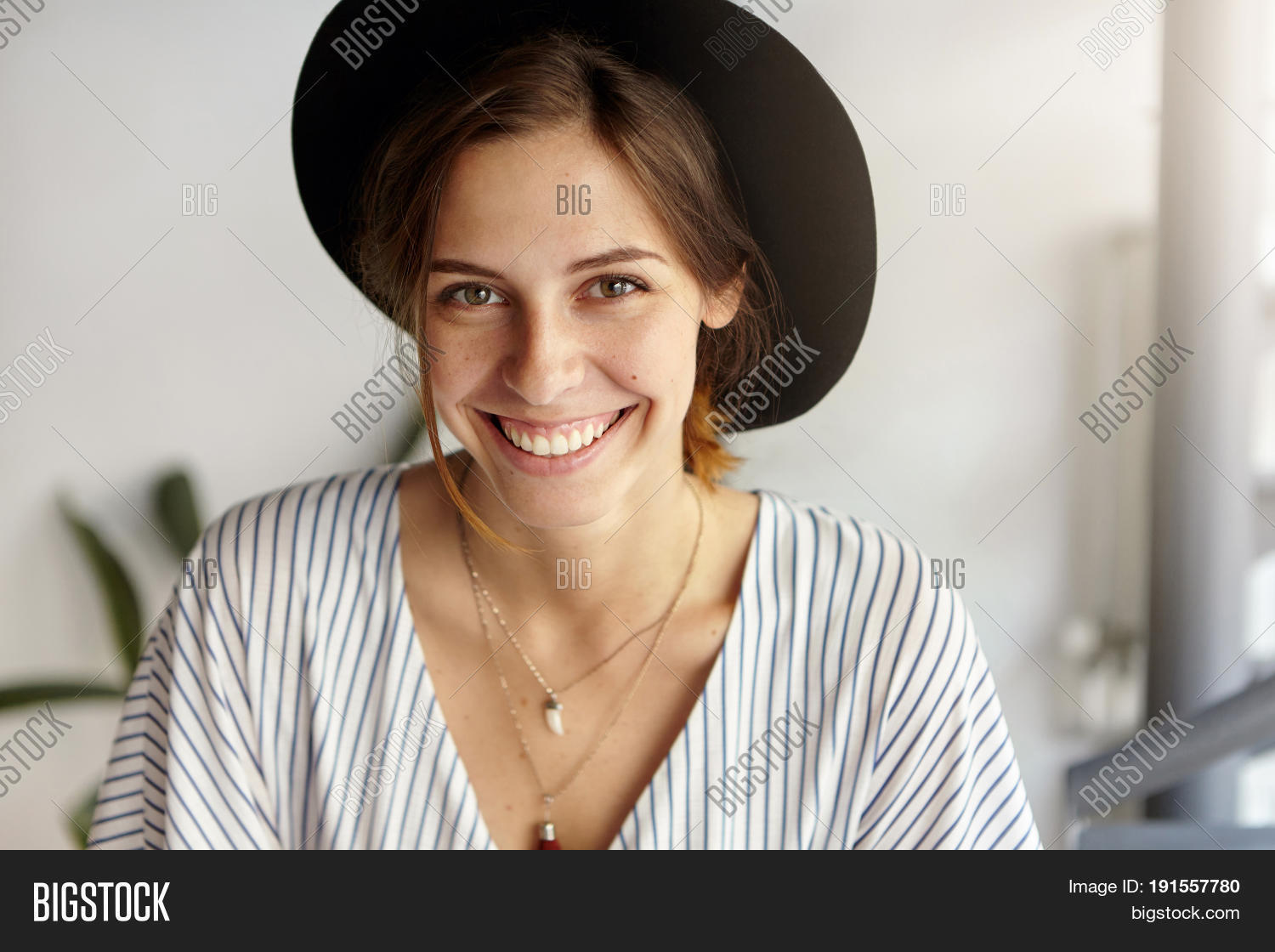 f840109f99ab6 Waist up portrait of beautiful European female with dark eyes warm smile  and dark hair wearing black hat and blouse posing in camera having good  mood.