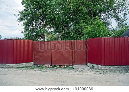 Red metal fence with  and wicket near the road