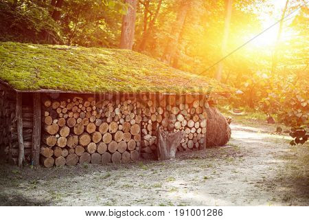 wooden house with accurately precisely gathered together firewood logs with beutiful sunset on the background