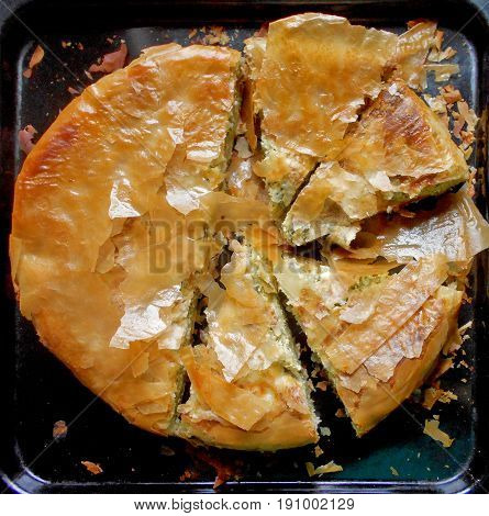 Chopped rounded pie with cheese and green, leafy vegetables