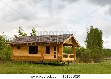 View Of The House Built Of Logs With A Roof Of Brown Metal