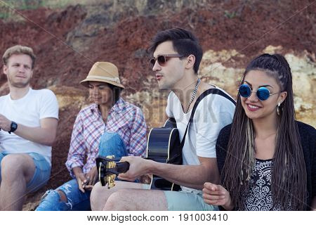 group of young and cheerful friends sitting on stones on beach. One man is playing guitar. Music outdoor