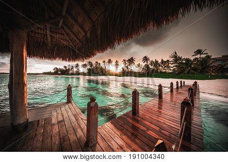 Beautiful view toward tropical beach and wooden water villa Punta Cana