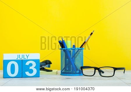 July 3rd. Image of july 3, calendar on yellow background with office supplies. Summer time. With empty space for text.