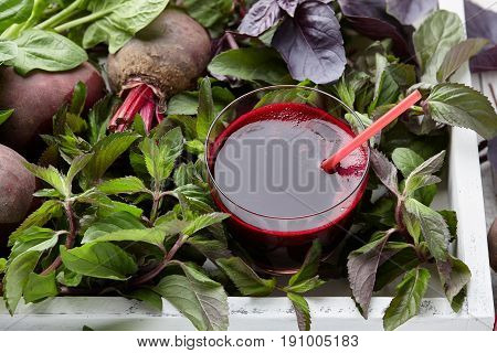 Fresh beetroot juice with herbs in white wooden tray