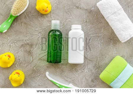 Baby care with bath cosmetic set, ducklings and towel on light gray background top view