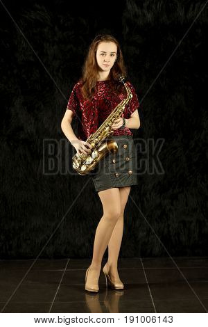 Portrait of a young girl with saxophone in a black room