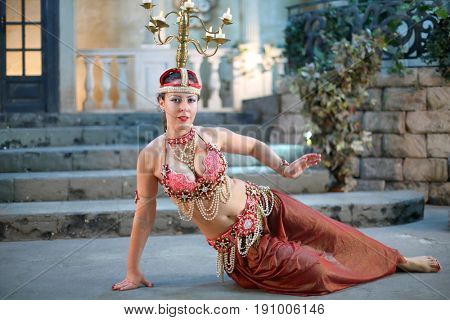 Beautiful woman in a dress decorated with pearls and chandelier on her head lies on the floor