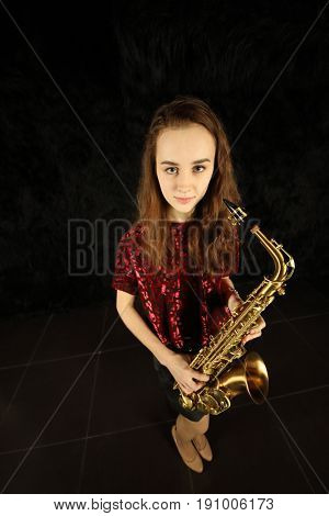 Portrait of young girl with saxophone in a black room, top view