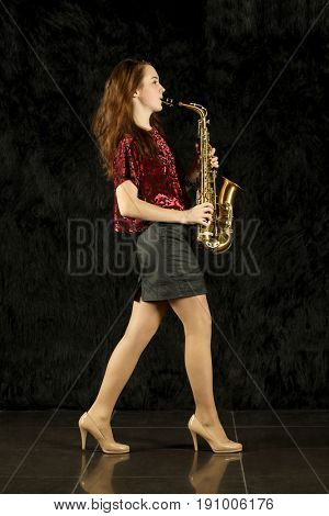 Young girl playing saxophone in a black room