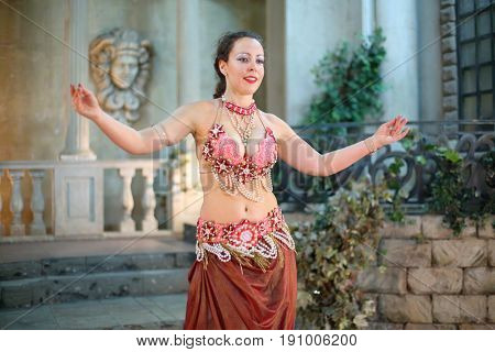 Portrait of beautiful woman in a red dress decorated with pearls is dancing Arabic dance