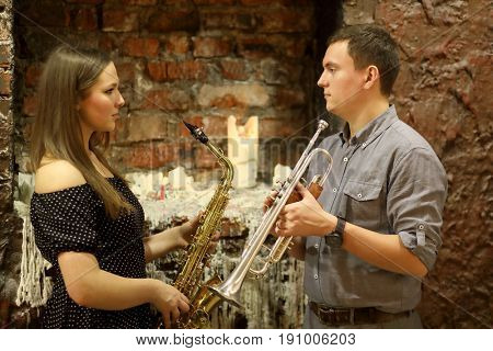 Two musicians with wind instruments in their hands look at each other in front a brick wall with a candle and a wax coating