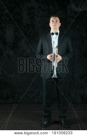 Portrait of a man in a black suit with a trumpet in his hands on a black fur ground