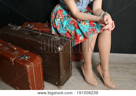A woman in a floral skirt and high heels sitting on old suitcases