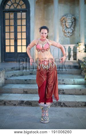 Beautiful woman in a red dress decorated with pearls is dancing on the drum