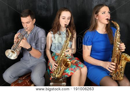 Man and two girls playing wind instruments sitting on old suitcases in front of black wall