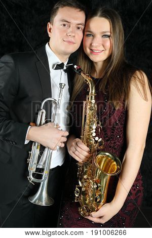 Portrait of happy musicians with wind instruments in their hands on a black fur ground