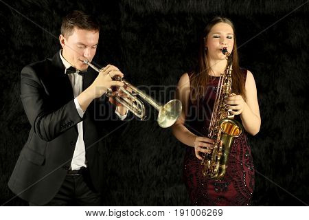 Two jazz musicians playing on wind instruments in a black room