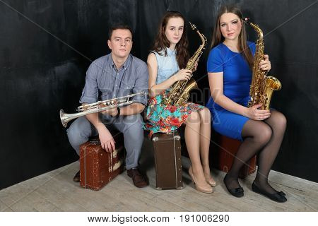 Three musicians with wind instruments in their hands sitting on old suitcases